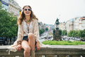 Laughing trendy hippie woman relaxing on stone parapet in prague brunette tourist wenceslas square the background saint Royalty Free Stock Photos