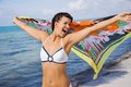Laughing vivacious woman at the seaside in a bikini holding a colourful patterned scarf in her outstretched hands to flutter in Stock Image