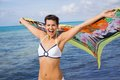 Laughing vivacious woman at the seaside in a bikini holding a colourful patterned scarf in her outstretched hands to flutter in Royalty Free Stock Photo