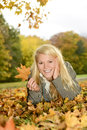 Laughing woman with autumn leave young blond lying on a meadow Stock Images