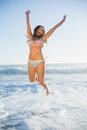 Laughing woman in bikini jumping in the sea on a sunny day Stock Photography
