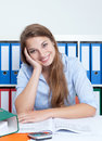 Laughing woman with blond hair at office has a break on her desk camera Royalty Free Stock Image