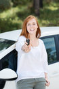 Laughing woman with a car key leaning back against her new showing off Royalty Free Stock Photography