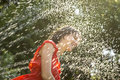 Laughing woman cooling off under a spray of water Royalty Free Stock Photo