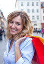 Laughing woman with curly blond hair and shopping bags in the city
