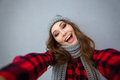 Laughing woman in hat and scarf making selfie photo Royalty Free Stock Photo