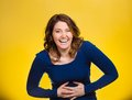 Laughing woman hearing good news joke portrait young smiling happy hands on stomach looking at camera isolated yellow background Stock Photo