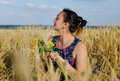 Laughing woman holding flowers in a wheat field Royalty Free Stock Photo