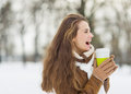 Laughing woman with hot beverage in winter park Stock Photos