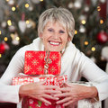 Laughing woman hugging a pile of christmas gifts beautiful senior to her chest as she sits in front decorated tree Royalty Free Stock Images
