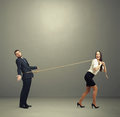 Laughing woman lugging man in perplexity Royalty Free Stock Photo