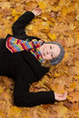 Laughing woman lying leaves fall young wrapped up in warm clothes on maple and full of joy Royalty Free Stock Photography