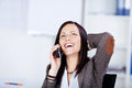 Laughing woman speaking on a telephone with her head tilted back in enjoyment while seated indoors Royalty Free Stock Images