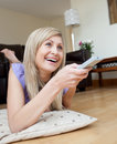 Laughing woman watching TV lying on the floor Stock Images