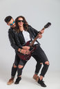 Laughing woman plays electric guitar with her man Royalty Free Stock Photo