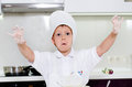 Laughing young boy with floury hands showing them to the camera as he stands in the kitchen learning to bake Royalty Free Stock Image