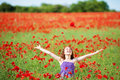 Laughing young girl in a poppy field surrounded by red flowers looking up into the sunshine with her arms outstretched Stock Photo