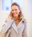Laughing young pretty woman using a mobile phone Stock Image