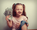 Laughing young winner holding dollar with closed eye. Happy kid Royalty Free Stock Photo