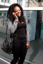 Laughing young woman chatting on a mobile phone or cellphone as she stands sidewalk an urban street smiling with happiness Royalty Free Stock Photography