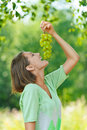 Laughing young woman eating grapes Royalty Free Stock Images