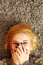 Laughing young woman lying on the carpet closeup portrait of a at home Stock Photography