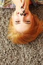Laughing young woman lying on the carpet at home Royalty Free Stock Images