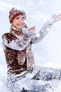 Laughing young woman playing with snow outdoors Royalty Free Stock Image