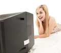 Laughing young woman watching television Royalty Free Stock Photo