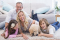 Laughting family with their pet yellow labrador on the rug Royalty Free Stock Photo