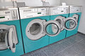 Laundrette machines washing in a public launderette Royalty Free Stock Photos