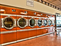 Laundromat retro style with dark orange dryers Stock Photo