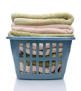 Laundry basket with folded towels closeup of a filled the blue plastic is isolated on white reflection Royalty Free Stock Photos