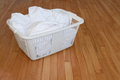 Laundry basket with white towels on wooden floor Royalty Free Stock Image