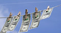 Laundry money one dollar bills on line attached with wooden clips over blue sky Royalty Free Stock Photos