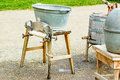 Laundry old fashioned mangle with washing tub on top and crank at side several old utensils partly visible to the right ground is Stock Image