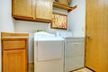 Laundry room small with wooden cabinets and white appliances Stock Images