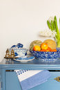 Lavender colored cabinet with antique old crockery and fruit Stock Photography