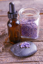 Lavender essential oil with lavendula flowers on the rock and in the jar dry leaves of this herb near the bottle Royalty Free Stock Image