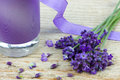 Lavender oil bottle of with purple ribbon and flowers on a wooden background Royalty Free Stock Images