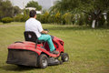 Lawn mower cutting grass Stock Photos