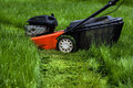 Lawn mower in garden standing a Royalty Free Stock Photos