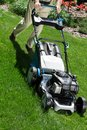 Lawn mower on green lawn Royalty Free Stock Photo