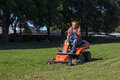 Lawn mower man driving a in the city park Stock Image