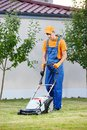Lawn mower worker man cutting grass in garden yard Royalty Free Stock Photography
