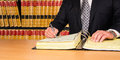 Lawyer signing legal documents with law books in the background Royalty Free Stock Photo