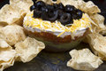 Layered bean dip and corn chips in glass bowl topped with black olives surrounded with Royalty Free Stock Photo