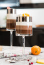 Layered chocolate desserts in glasses. Slices of mandarine on a top of sweet. Selective focus Royalty Free Stock Photo