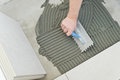 Laying ceramic tiles troweling mortar onto a concrete floor in preparation for white floor tile Royalty Free Stock Images