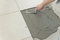 Laying ceramic tiles troweling mortar onto a concrete floor in preparation for white floor tile Stock Photos